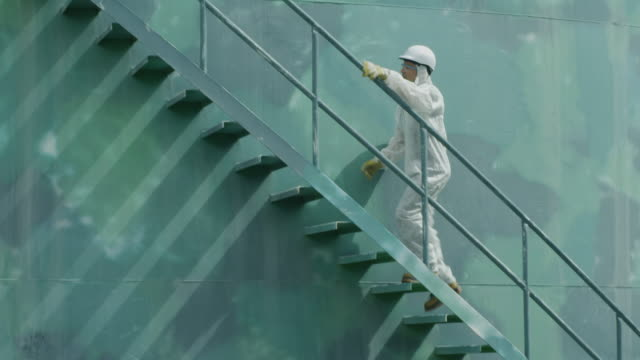 LS worker in protective coverall ascending stairs on storage tank; camera follows him up, RED R3D 4K