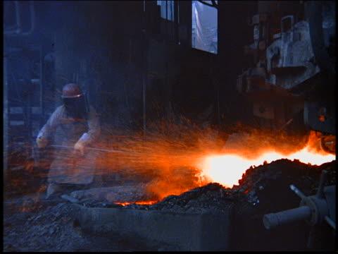 vídeos de stock, filmes e b-roll de worker in protective gear poking metal pole into furnace in steel mill / brazil - metarlúgica