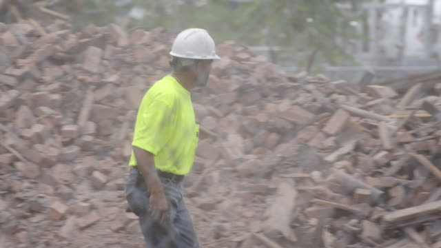 Worker in scrap yard wearing a hard hat and yellow shirt walking past piles of junk and recycling debris. Slow motion.