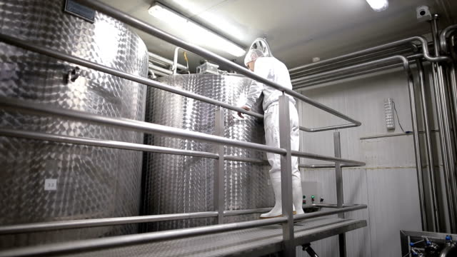 worker in the food factory opens the pasteurization tank. dairy products - dairy factory stock videos & royalty-free footage