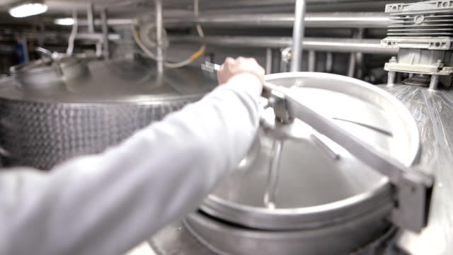 worker in the food factory opens the pasteurization tank. dairy products - milk stock videos & royalty-free footage