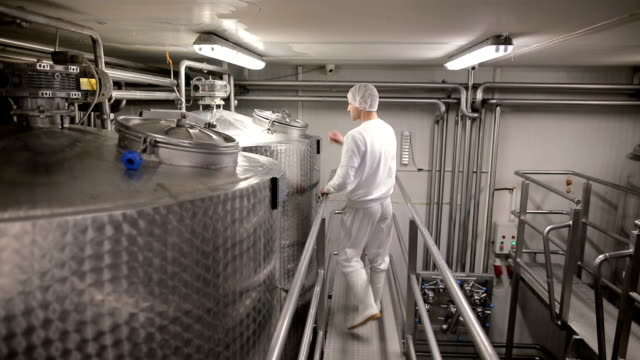 Worker in the food factory opens the pasteurization tank. Dairy products