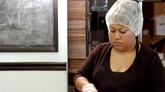 ms tu worker in toffee shop spreads hot chocolate over slabs of toffee in baking trays / rancho mirage, california, usa - chocolate factory stock videos & royalty-free footage