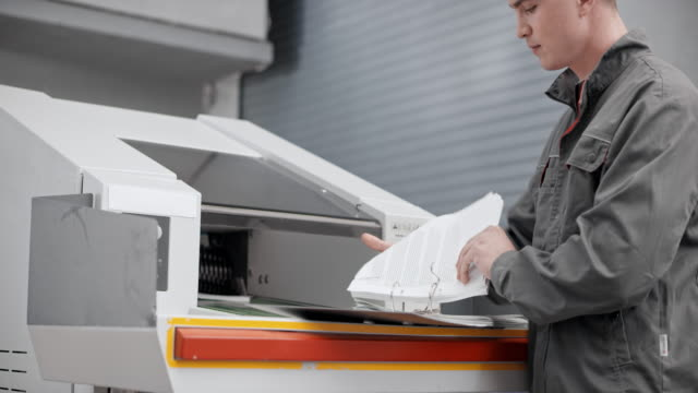 ds ワーカーの工業用シュレッダーにドキュメントを挿入します。 - 全壊点の映像素材/bロール