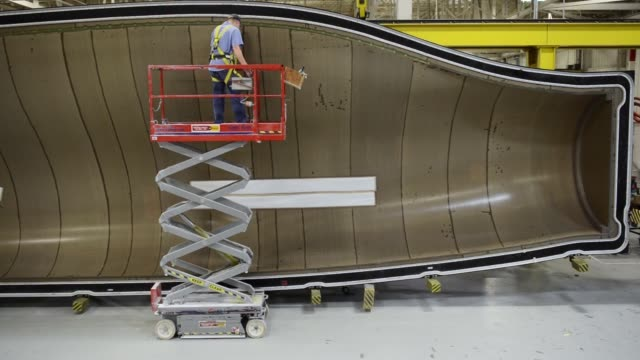 A worker inspects a blade mold at the Siemens wind turbine blade plant in Fort Madison Iowa A worker cuts fiberglass fabric as part of the production...