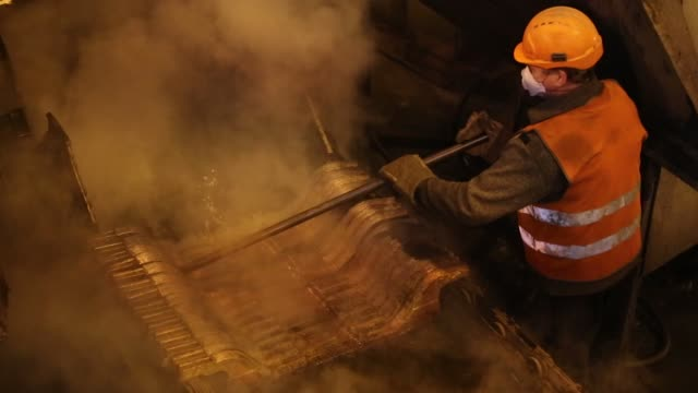 worker inspects a copper cathode sheet as it cools in its mold in the copper smelting shop at the uralelectromed ojsc copper refinery, operated by... - power equipment stock videos & royalty-free footage