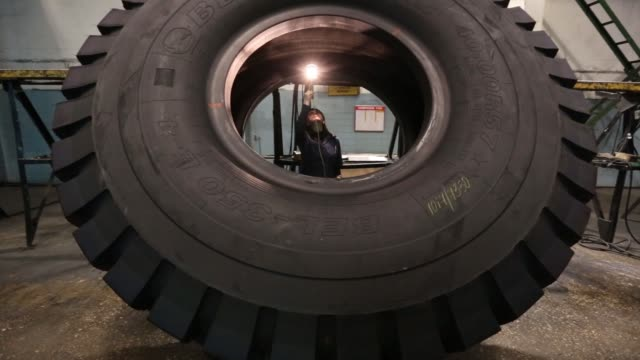 a worker inspects a large 4000r57 sized tire in the control room at the belshina jsc tire factory in babruysk belarus on thursday march 16 a worker... - ゴム点の映像素材/bロール
