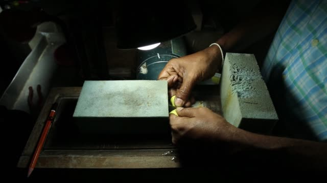 worker inspects a rough gemstone while cutting at a workshop in ratnapura, sri lanka, on wednesday, feb. 7 a worker cuts a rough gemstone at a... - precious gemstone stock videos & royalty-free footage