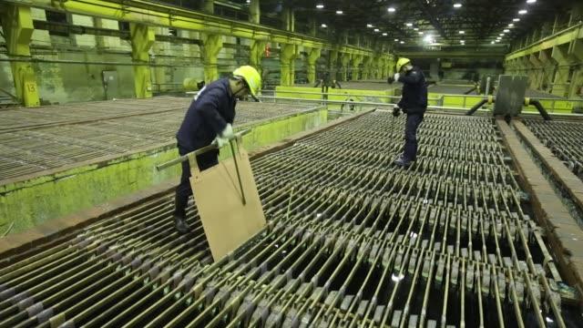 a worker inspects copper cathode sheets in an electrolytic tank inside the electrolysis shop at the mmc norilsk nickel pjsc copper refinery in... - moneta da 5 centesimi statunitensi video stock e b–roll