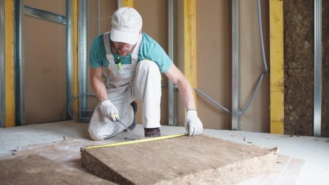 vidéos et rushes de ouvrier installant la laine minérale de roche pour l'isolation - un seul homme d'âge moyen