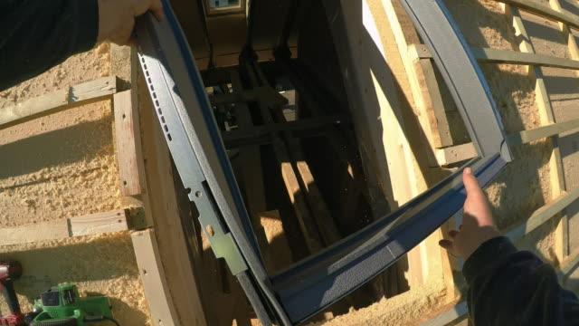 vídeos de stock, filmes e b-roll de pov worker instalando o quadro para a janela do telhado - establishing shot