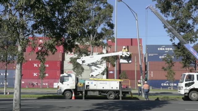 a worker installs a parking sign on a light post in the docklands precinct of melbourne australia on monday aug 15 workers inspect a damaged street... - tea light stock videos and b-roll footage