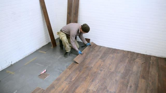 vidéos et rushes de travailleur installe stratifié marron dans la salle. - planche de bois