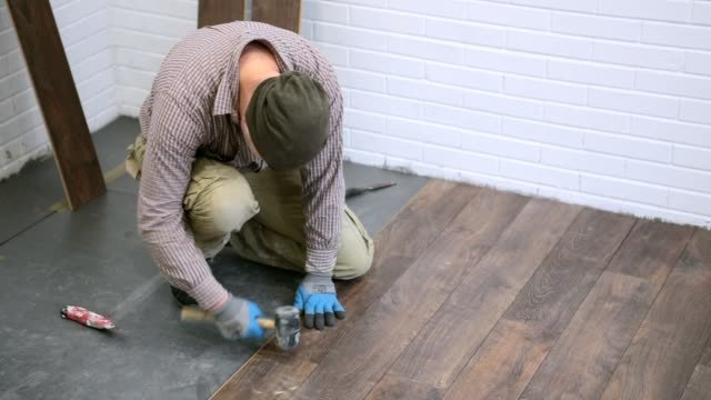 worker installs brown laminate in the room. - diy stock videos & royalty-free footage