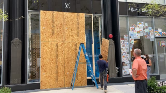 worker installs plywood in front of the windows as he make repairs to the louis vuitton store on michigan avenue after it was looted on august 10,... - other stock videos & royalty-free footage