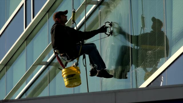 worker is cleaning high rise building window glass for a company located in chattanooga - lavoratore emigrante video stock e b–roll