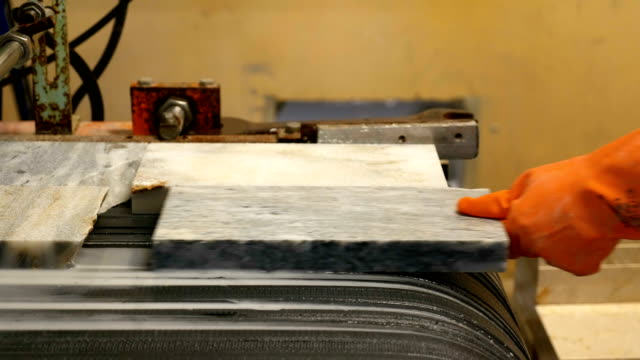 Worker is holding marble in production line in marble factory