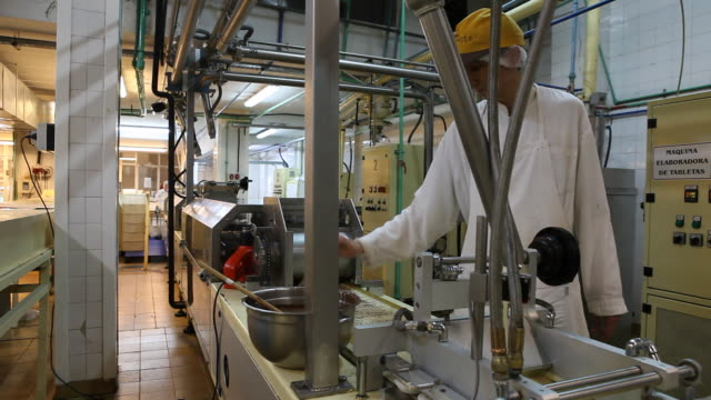 A worker is producing with a machine chocolate products in the chocolate factory 'Del Turista' in Bariloche in Patagonia