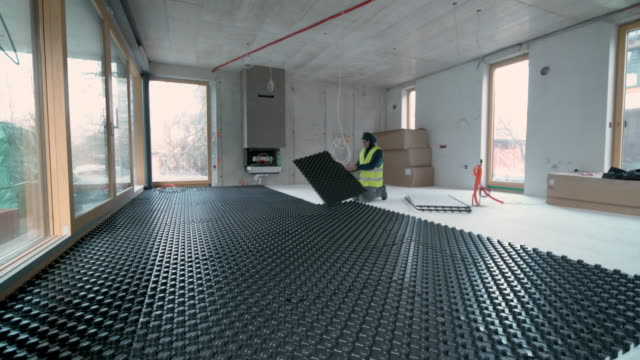 ds worker laying black insulation panels for floor heating - installing stock videos & royalty-free footage