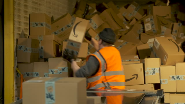 worker loads a truck with packages at an amazon packaging center on november 28, 2019 in brieselang, germany. amazon is anticipating a strong holiday... - amazon region stock videos & royalty-free footage