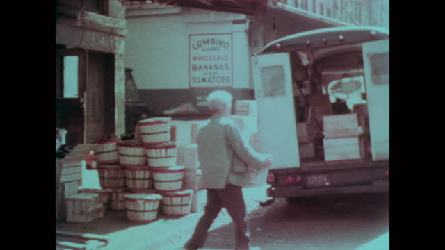 1967 Worker loads fruit into the back of a delivery truck