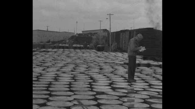 a worker looks over a list as he walks across the top of scores of barrels / vs men roll a barrel from a union pacific freight car to a flatbed truck... - alcan highway stock videos and b-roll footage