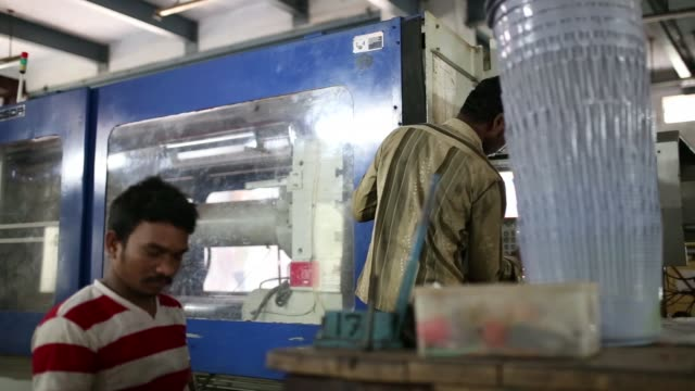 A worker looks over at the operation of an injection molding machine at the Bhupendra International facility in Chennai India on Tuesday Nov 28 A...