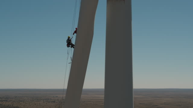 worker lowering down a wind turbine blade - safety harness stock videos & royalty-free footage