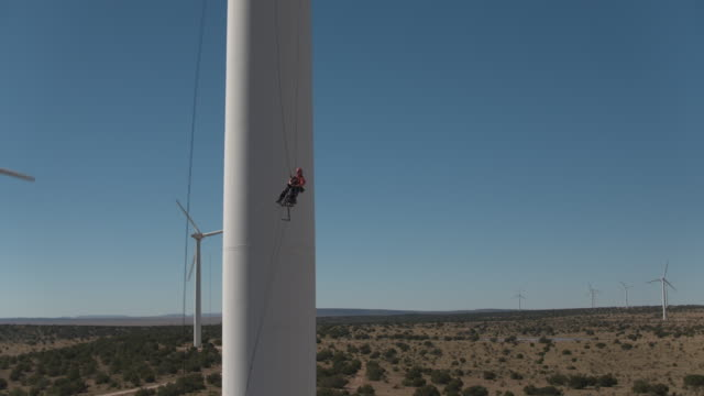 Worker lowering down turbine from ropes continued