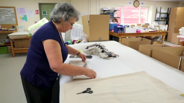 worker lynne needham folds and packages commemorative tea towels by victoria eggs to mark the wedding of prince harry to meghan markle at countryside... - souvenir stock videos and b-roll footage