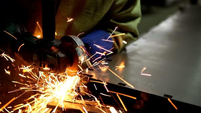 Arbetstagaren gör snitt på plåt av angule slipmaskinen.