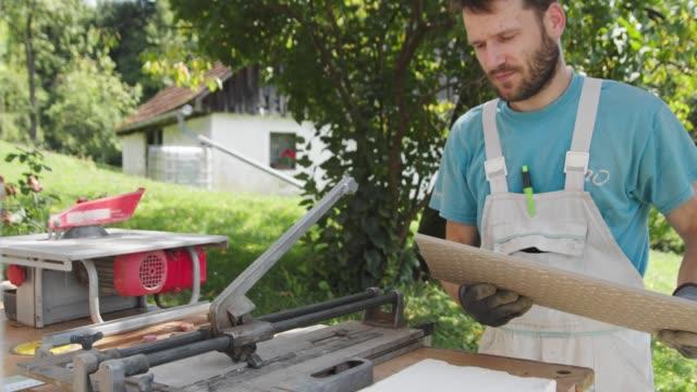 vídeos de stock e filmes b-roll de worker making a straight cut on a tile with a special machine - cerâmica