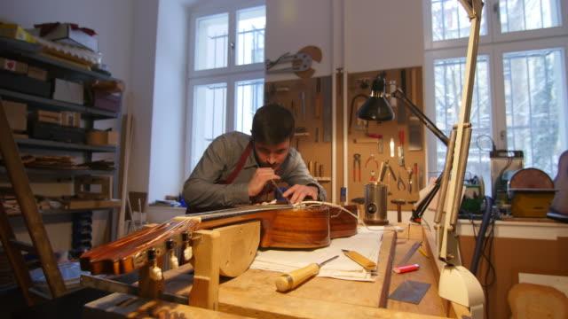 Worker making guitar at workshop