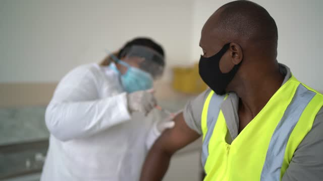 worker man being vaccinated - wearing face mask - epidemiology stock videos & royalty-free footage