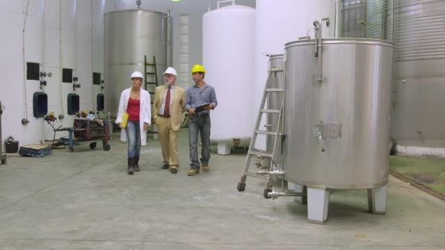 vidéos et rushes de ws pan worker, manager and lab technician walking through warehouse / sanlucar de barrameda, andalusia, spain - costume complet