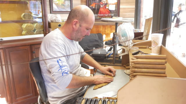 Worker manually rolling the worldwide famous Cuban cigars You don't have to go to Cuba to see this Florida is the place to go without the need of...