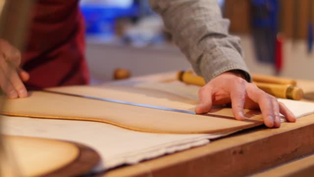 Worker measuring wood in guitar workshop