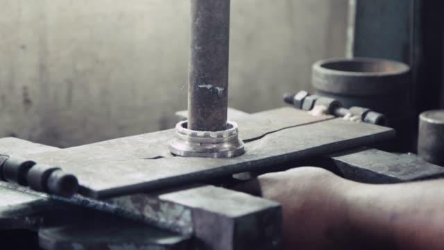 労働者のメカニックを固定し、ガレージのワークショップでベアリングホイールとブレーキシステムのスペアパーツを脱ぐためにベアリングホイールマシンを押す使用。 - 交代点の映像素材/bロール