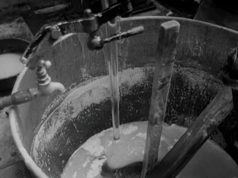 A worker mixes glucose sugar and water together in a huge bowl in a sweet factory 1951