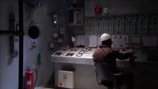 vídeos de stock, filmes e b-roll de a worker monitors a control panel. - capacete de trabalho
