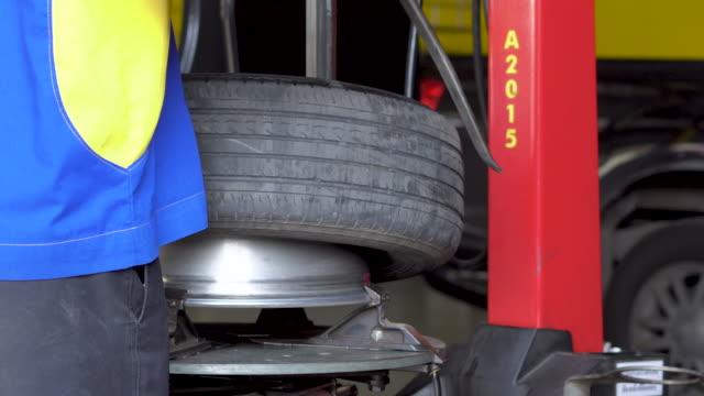 vídeos y material grabado en eventos de stock de neumático de montaje del trabajador en la llanta de la rueda utilizando una máquina especial. - brazo humano