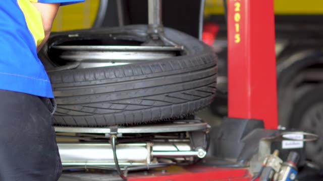 vídeos y material grabado en eventos de stock de neumático de montaje del trabajador en la llanta de la rueda utilizando una máquina especial. - part of a series