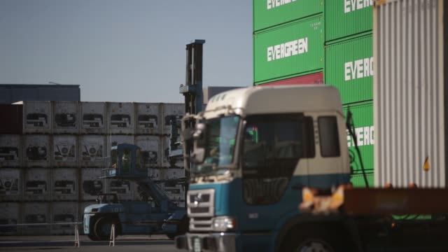 A worker moves a container with a forklift while a truck carrying a container drives into a container terminal Workers operate forklifts at a...