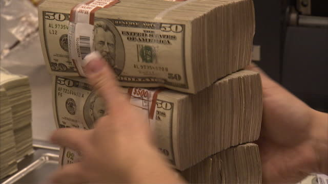CU ZO Worker moving stacks of 50 dollar bills on table / Kansas City, Kansas, United States