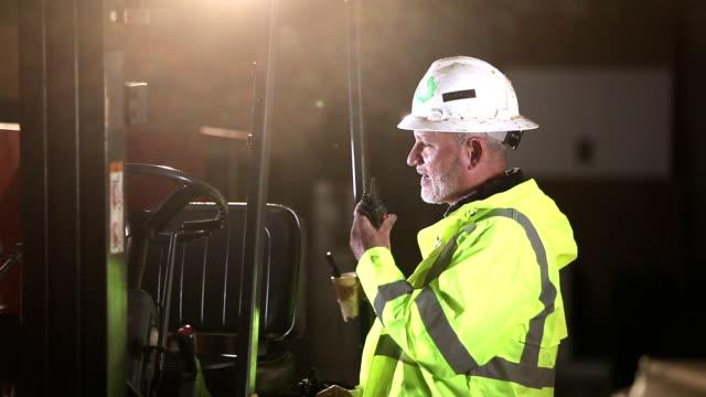 vídeos y material grabado en eventos de stock de trabajador junto a carretilla elevadora hablando en walkie-talkie - walkie talkie