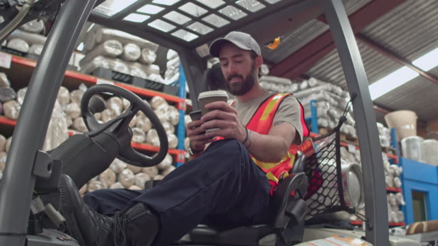 Worker on forklift having his coffee break at warehouse