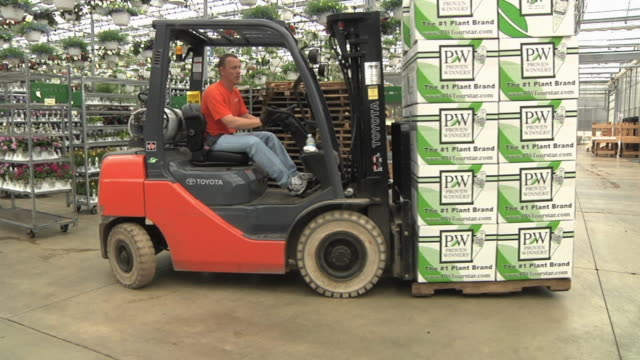 slo mo ws pan worker on forklift loading stack of cardboard boxes into loading dock at commercial greenhouse, carleton, michigan, usa - gewächshäuser stock-videos und b-roll-filmmaterial