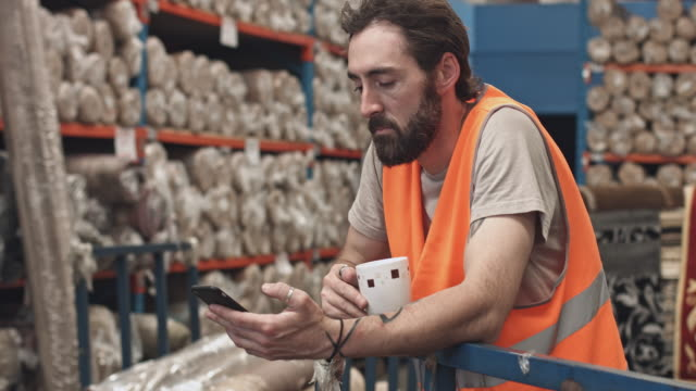 worker on his coffee break checking his mobile phone at warehouse - dialling stock videos & royalty-free footage