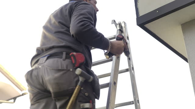 worker on roof installing metal tile - ladder stock videos & royalty-free footage
