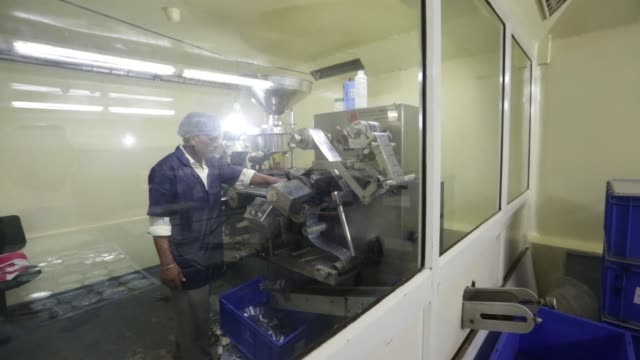 a worker operates a blister packing machine at the factory of jain's cow urine therapy health clinic in indore madhya pradesh india on monday june 27... - madhya pradesh stock videos and b-roll footage